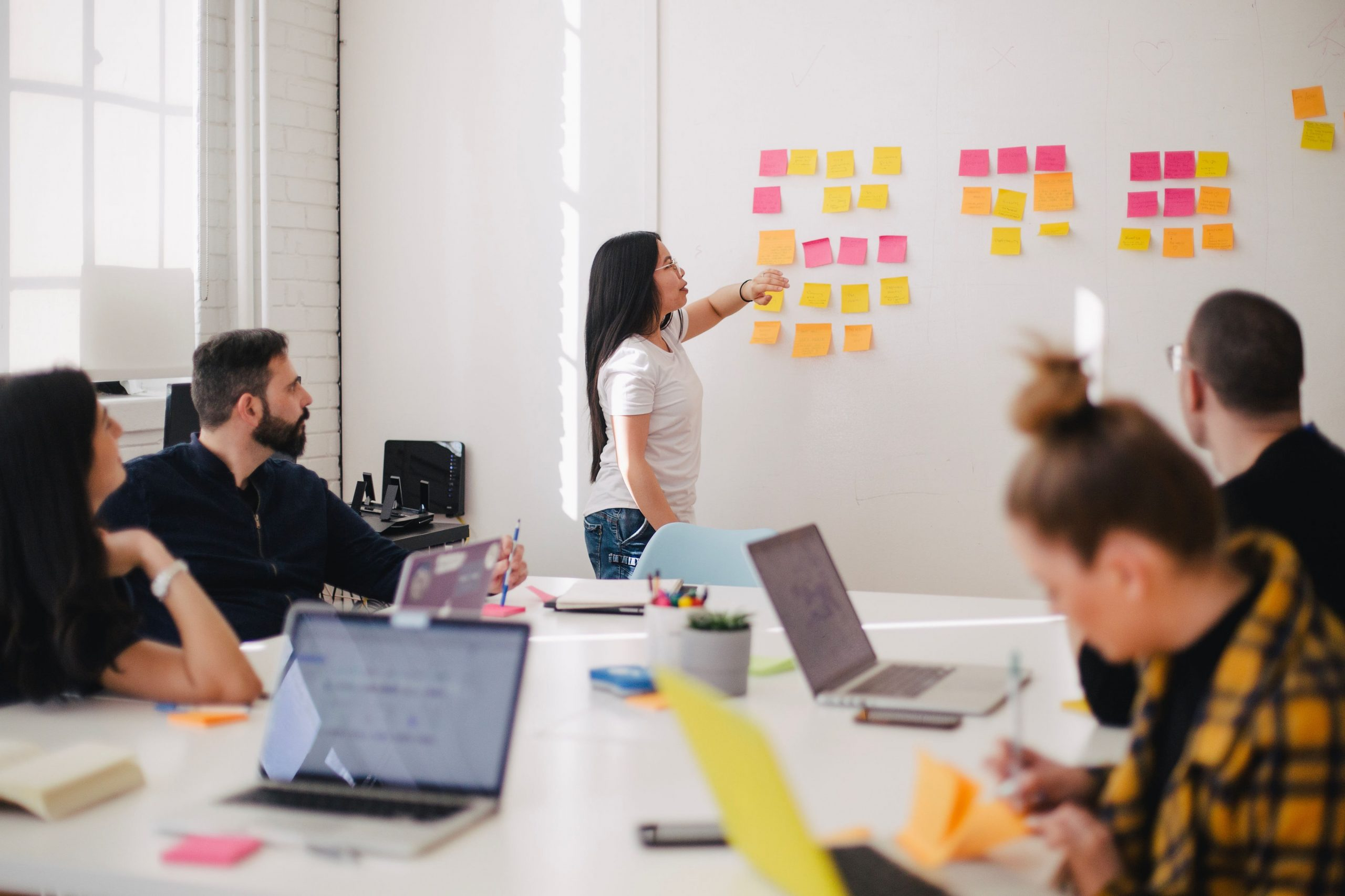 woman presenting to team in front of wall covered in post-it notes